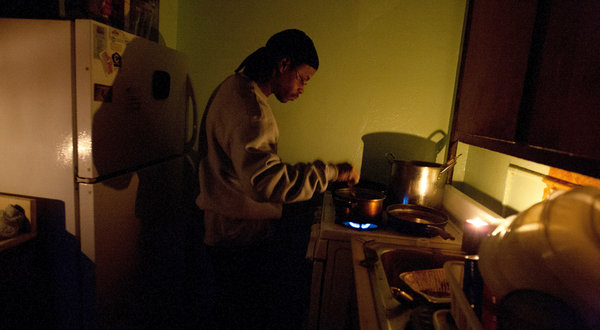 The gas is on, so Richard Bates can cook by candlelight, but life has been hard in Brooklyn's Red Hook Houses and for tens of thousands of other public housing residents without heat, water or power since Hurricane Sandy hit. No lights or elevators function in their 12-story buildings. – Photo: Ruth Fremson, New York Times