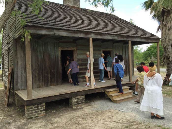 Visitors took a close look at a slave cabin at Whitney Plantation.